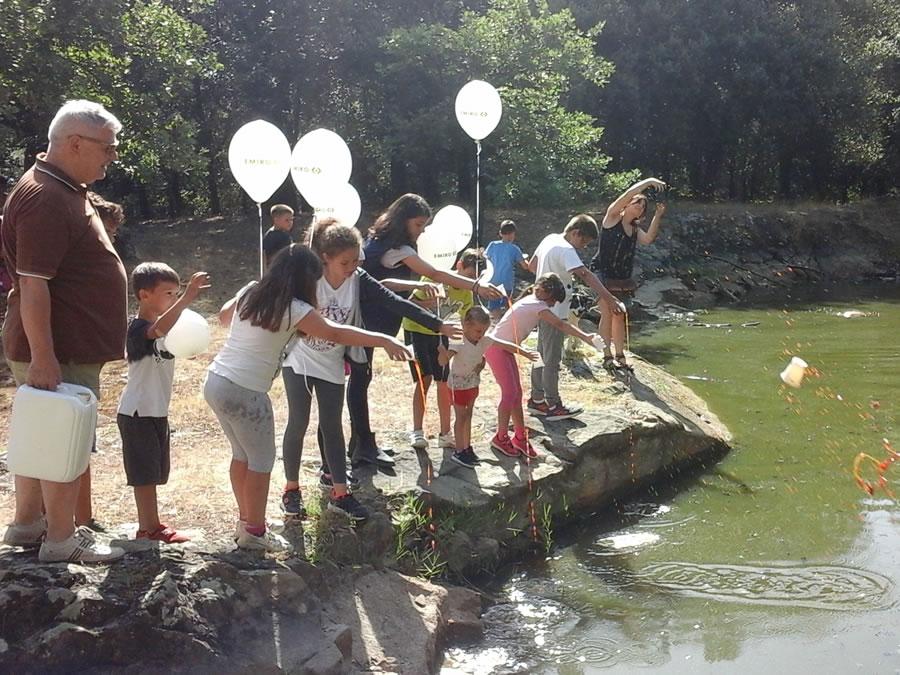 I bambini gettano palle di fango ed EM nello stagno